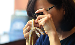 One of our auction jewelry appraisers examining a necklace